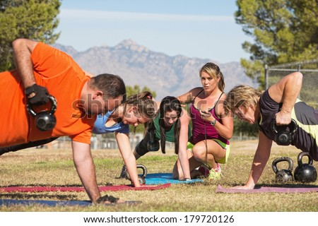 Instructor holding stopwatch while teaching bootcamp fitness - stock photo