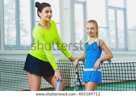 Instructor or tennis coach and girl posing on a court indoor - stock photo