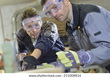 Instructor showing trainee how to use sawing machine - stock photo