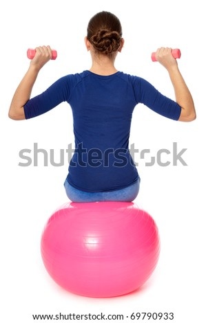 Instructor taking exercise class using ball and dumbbells at gym - stock photo