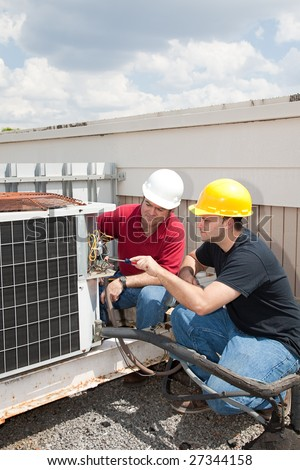 Instructor trains student to repair air conditioning compressor. - stock photo