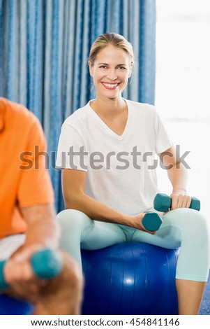 Instructor using exercise ball and weights during sports class - stock photo
