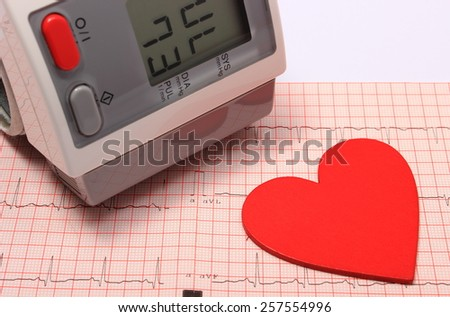 Instrument for measuring blood pressure and red heart shape on electrocardiogram graph, ekg heart rhythm, medicine concept - stock photo
