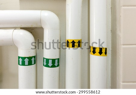 Insulated industrial water pipes with arrows marking the direction of water flow for inflow and outflow. (Yellow for heated water and green for chilled water.) - stock photo