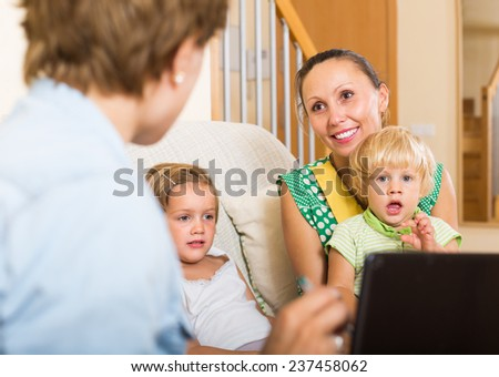 Insurance agent consulting smiling woman with two children at home  - stock photo