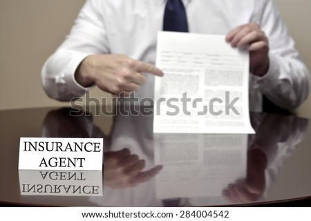 Insurance agent sitting at desk holding blank contract  - stock photo
