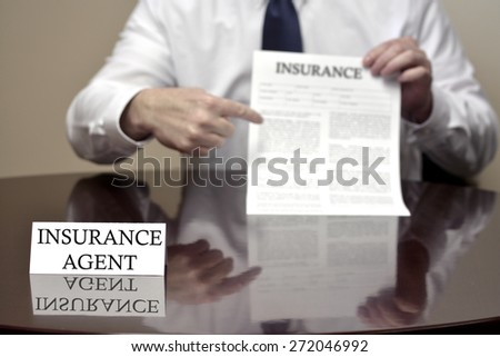 Insurance agent sitting at desk holding insurance contract