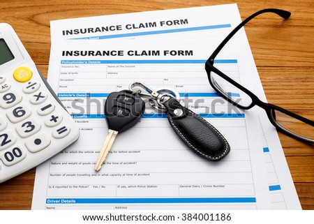 Insurance claim concept with car key and calculator on wood desk