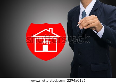 Insurance concept. Business man drawing shield protecting family and house. - stock photo