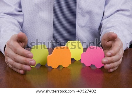 Insurance concept - Business man protecting many cars with his hands