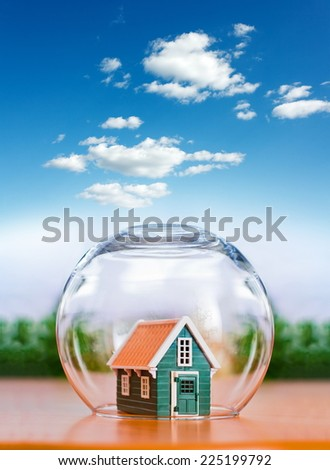 Insured house protected in glass sphere, under the cloudy bright sky - stock photo