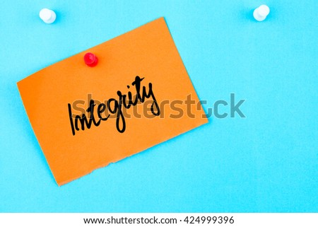 Integrity written on orange paper note pinned on cork board with white thumbtack, copy space available