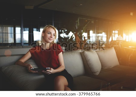 Intelligent businesswoman holding touch pad and dreaming about growth her career while resting in cafe,young female manager waiting for e-mail on digital tablet while sitting in modern office interior - stock photo