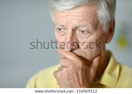 Intelligent elderly man in full vigor thinking on gray background