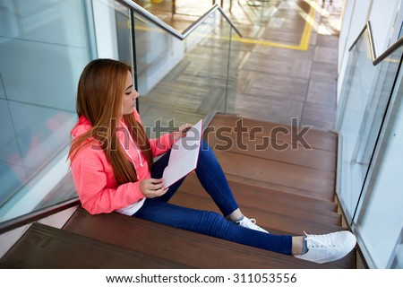 Intelligent female student reads her copybook while sitting on the wooden stairs of university hallway, stylish hipster girl preparing for classes or exams at college indoors campus, learning hard - stock photo