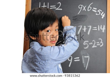Intelligent schoolboy writing on blackboard ( good at figures ) - stock photo
