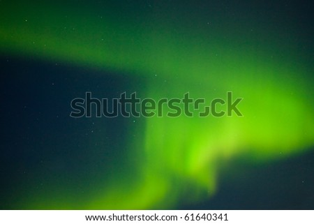 Intense Aurora borealis (northern lights) and lots of stars. - stock photo