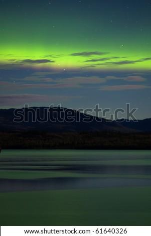 Intense Aurora borealis (northern lights) showing between clouds during moon lit night being mirrored on Lake Laberge, Yukon Territory, Canada. - stock photo