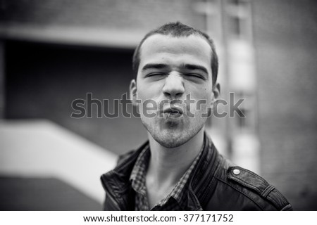 Intense black and white portrait of  man in leather jacket outdoors - stock photo