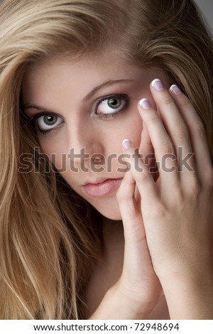 Intense close-up of pretty teenage girl with big eyes and beautiful hair and nails - stock photo