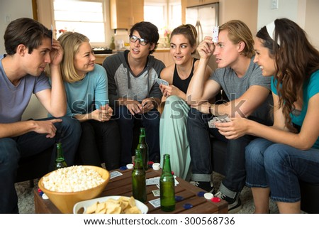 Intense game of poker between friends playing cards indoors party drinking beer - stock photo
