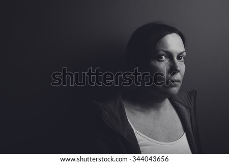 Intense low key portrait of pensive sad woman leaning on gray room wall, low contrast monochromatic image - stock photo