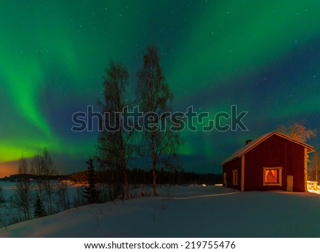 Intense northern lights - Aurora borealis over Lake and red House in Finland - stock photo