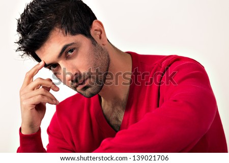Intense portrait of a man with his hand on the face, close up of a handsome Indian man - stock photo
