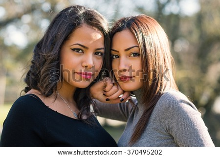 Intense portrait of young sisters outdoors in a park. - stock photo
