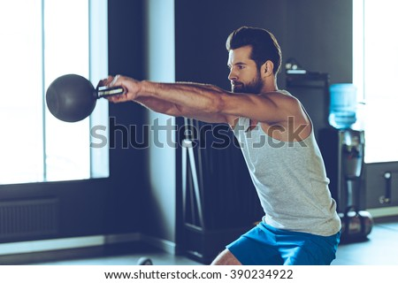 Intensive cross training. Side view of young handsome man in sportswear working out with kettle bell at gym - stock photo