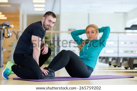 Intensive training together. Couple of young and beautiful people is having workout in a gym. Both are having abdominals training. Perfect shape. Sportsmen. - stock photo