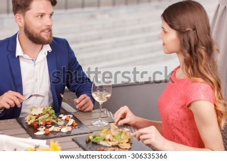 Intent glance. Beautiful couple having meal and looking at each other in restaurant.