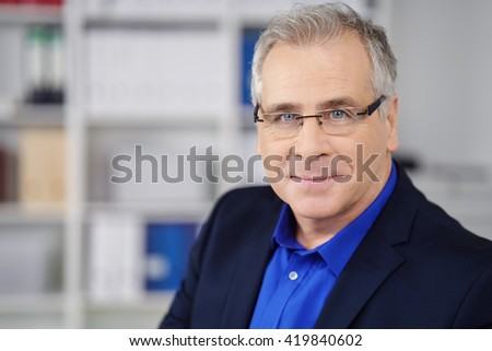 Intent middle-aged businessman wearing glasses looking directly at the lens with a quiet friendly smile, copy space - stock photo