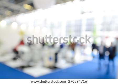 Intentionally blurred photo of people inside an exhibition. - stock photo