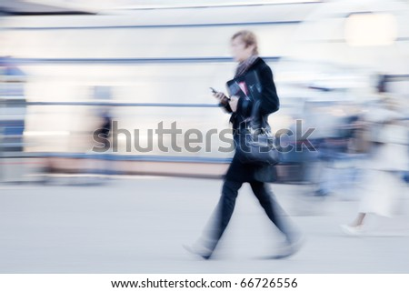 Intentionally motion blurred image of businesswoman with mobile phone in hand rushing to office in the morning - stock photo