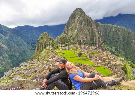 Inter ethnic couple of tourists on Sun Gate, (Machu Picchu, Peru) - stock photo