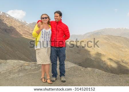 Inter ethnic couple of tourists posing on Tizi-n-Tichka pass, High Atlas mountains, Morocco - stock photo