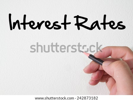 interest rates text concept on wall - stock photo