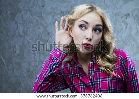interested young blond woman listening to something, studio shot - stock photo