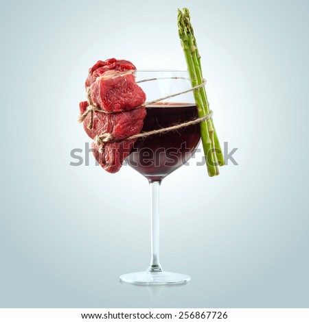 Interesting composition of meat and plants wiredly connected over the wine glass. - stock photo