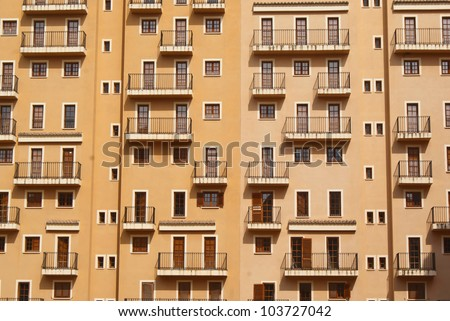 Interesting photo of building facade with windows, doors and balconies