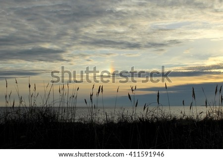 Interesting rainbow color referred to as a circumhorizontal arc  in the cloudy sunset sky at Hammonasset State Park in Madison, CT. - stock photo