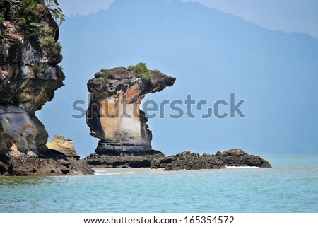 Interesting rock formation in south China sea. Seen from shore of Bako National Park, Malaysia (Borneo). Results from years of wind, water, sand erosion. - stock photo