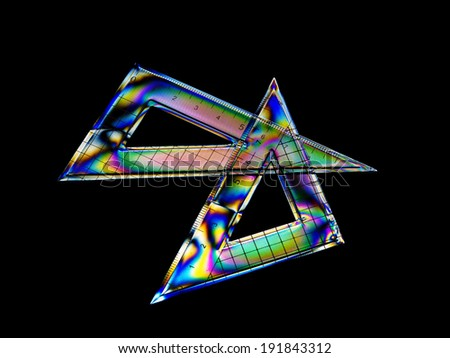 Interference stress pattern in plastic school geometry set squares. Rainbow colours, triangles. - stock photo