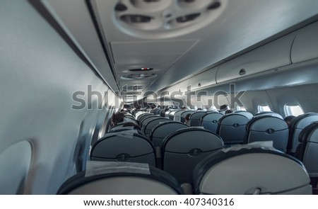 Interior airplane with passengers. Aircraft cabin after take off - stock photo