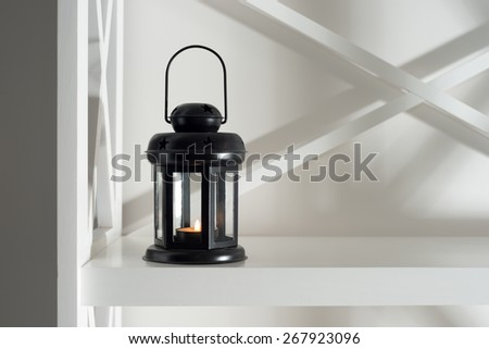 interior and decor in the room. black lantern with a candle on a white bookcase in the design of the room. - stock photo