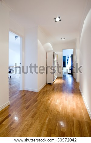 interior corridor with wood floor and furniture at a modern house - stock photo