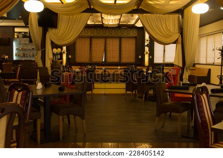 Interior decor of an empty nightclub with a small stage for live performances and tables and chairs for patrons