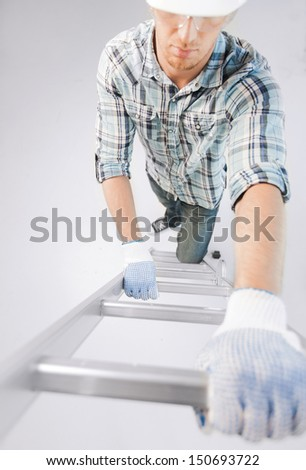 interior design and home renovation concept - man in helmet and gloves climbing ladder - stock photo