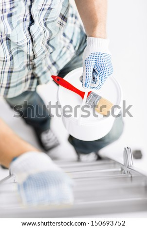 interior design and home renovation concept - man with paintbrush and paint pot climbing ladder - stock photo
